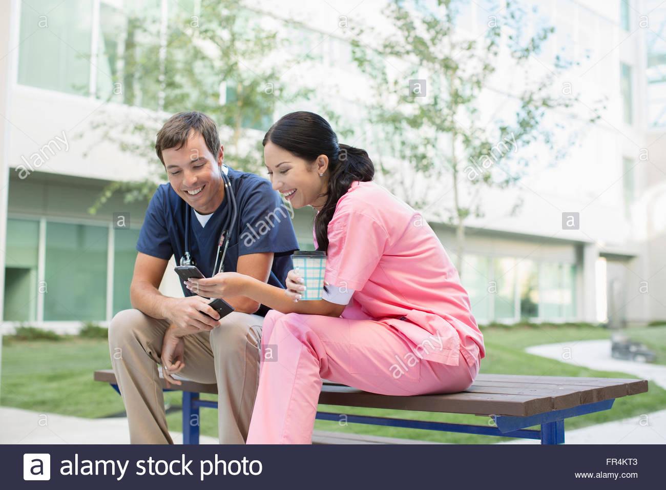I professionisti del settore medico in pausa guardando smartphone Immagini Stock