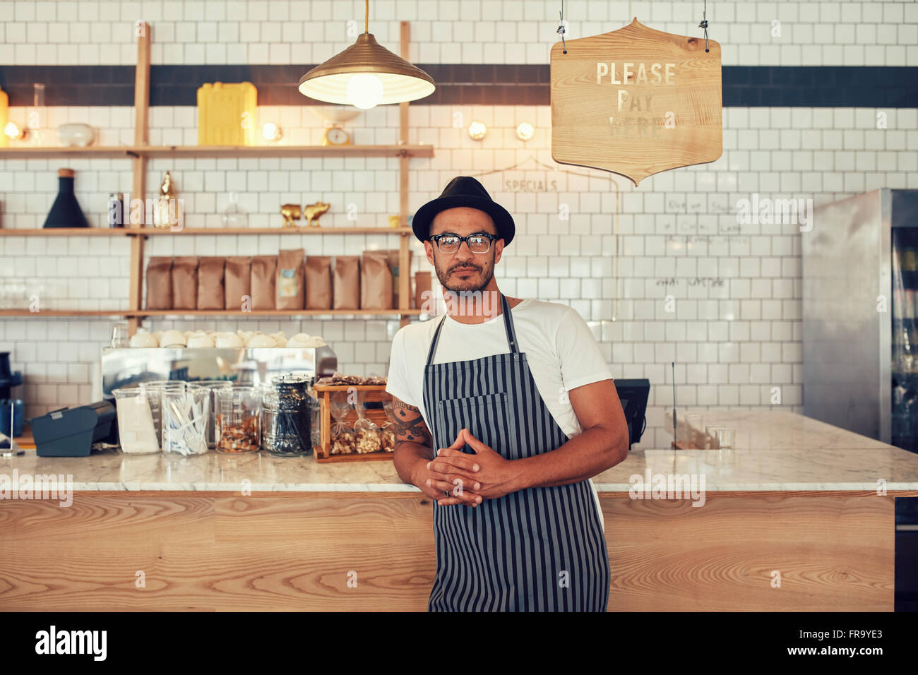 Ritratto di un giovane fiducioso coffee shop proprietario in piedi presso il cafe contatore. Bel giovane uomo che Immagini Stock
