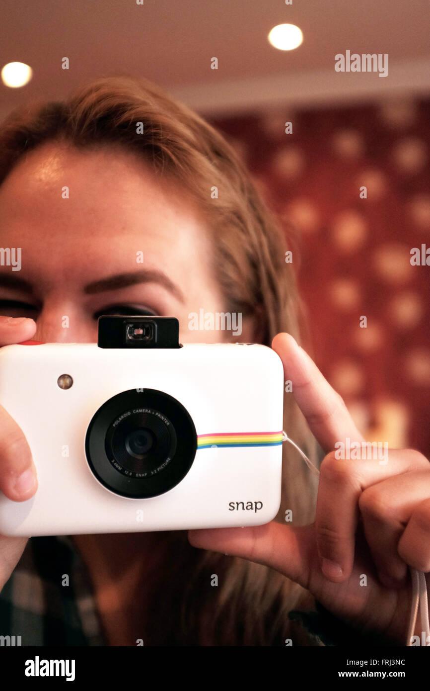 Giovane donna utilizzando una Polaroid fotocamera Snap per prendere la stampa istantanea di fotografie Immagini Stock