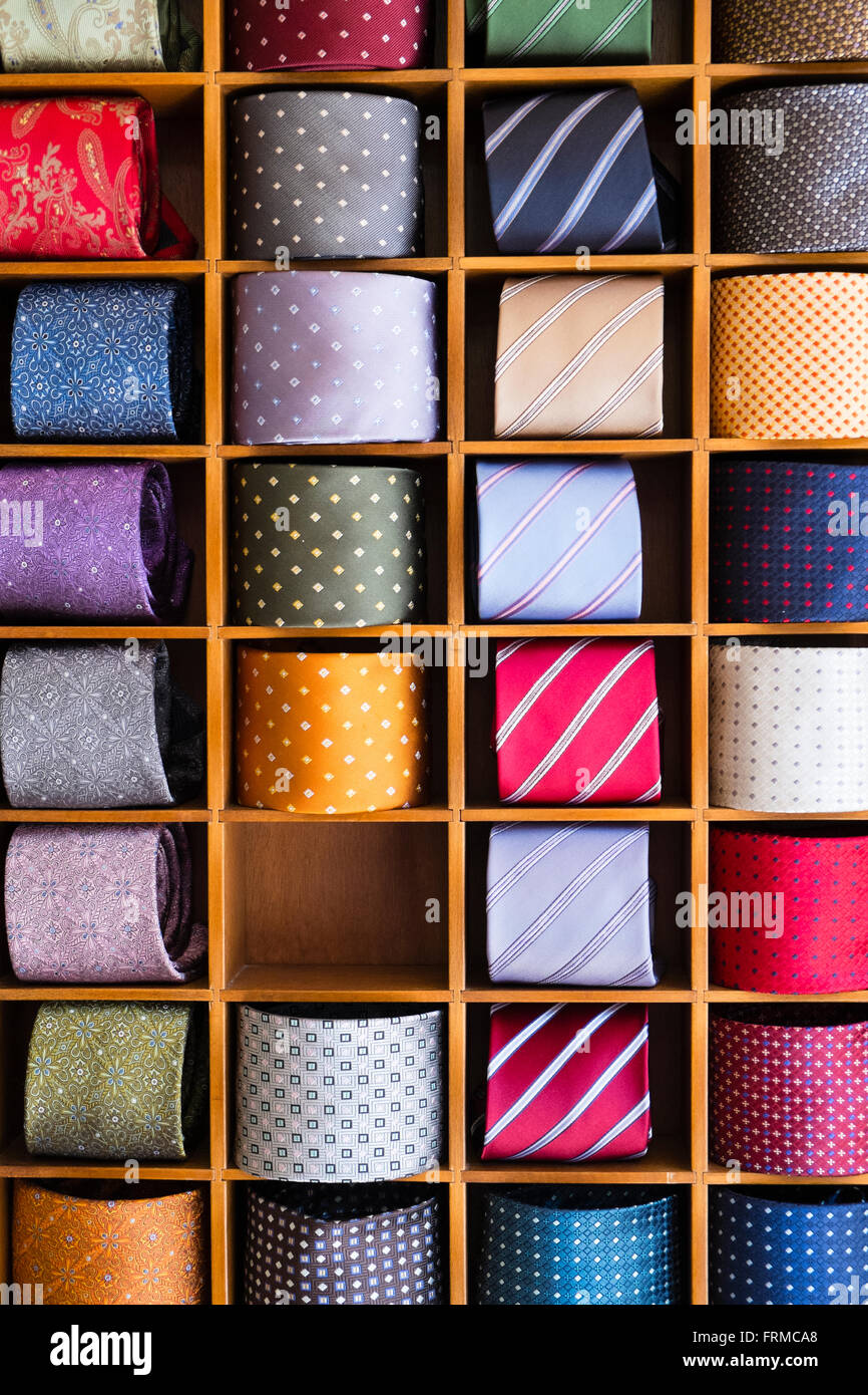 Il display di coloratissimi mens' cravatte, laminati e impostare tra le partizioni in legno, uno scomparto vuoto. Immagini Stock