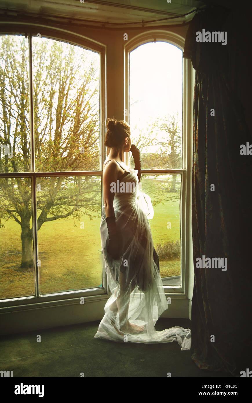 Giovane donna in piedi dalla finestra Immagini Stock