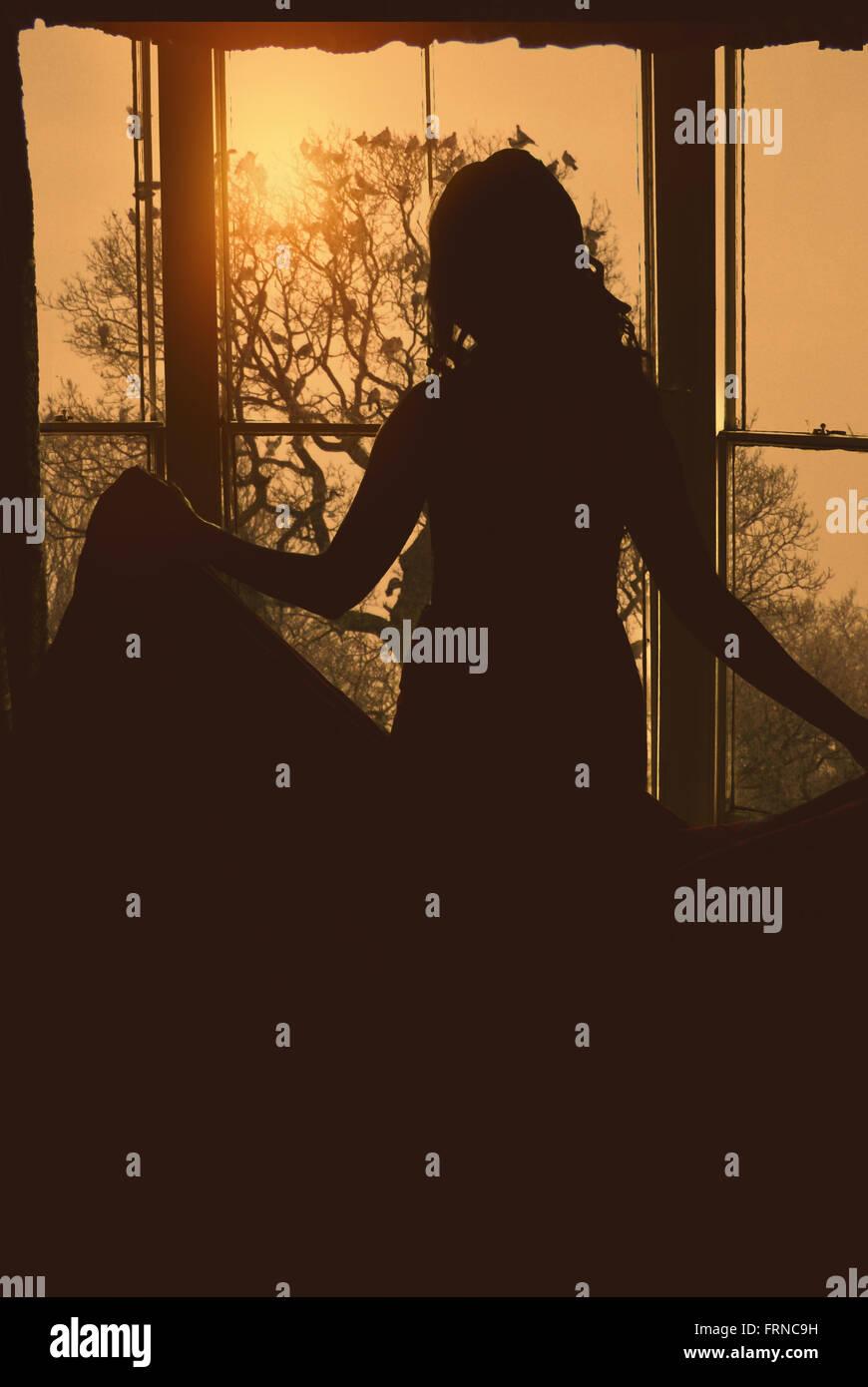 Silhouette del retro della giovane donna che mantiene il suo abito in piedi dalla grande finestra Immagini Stock