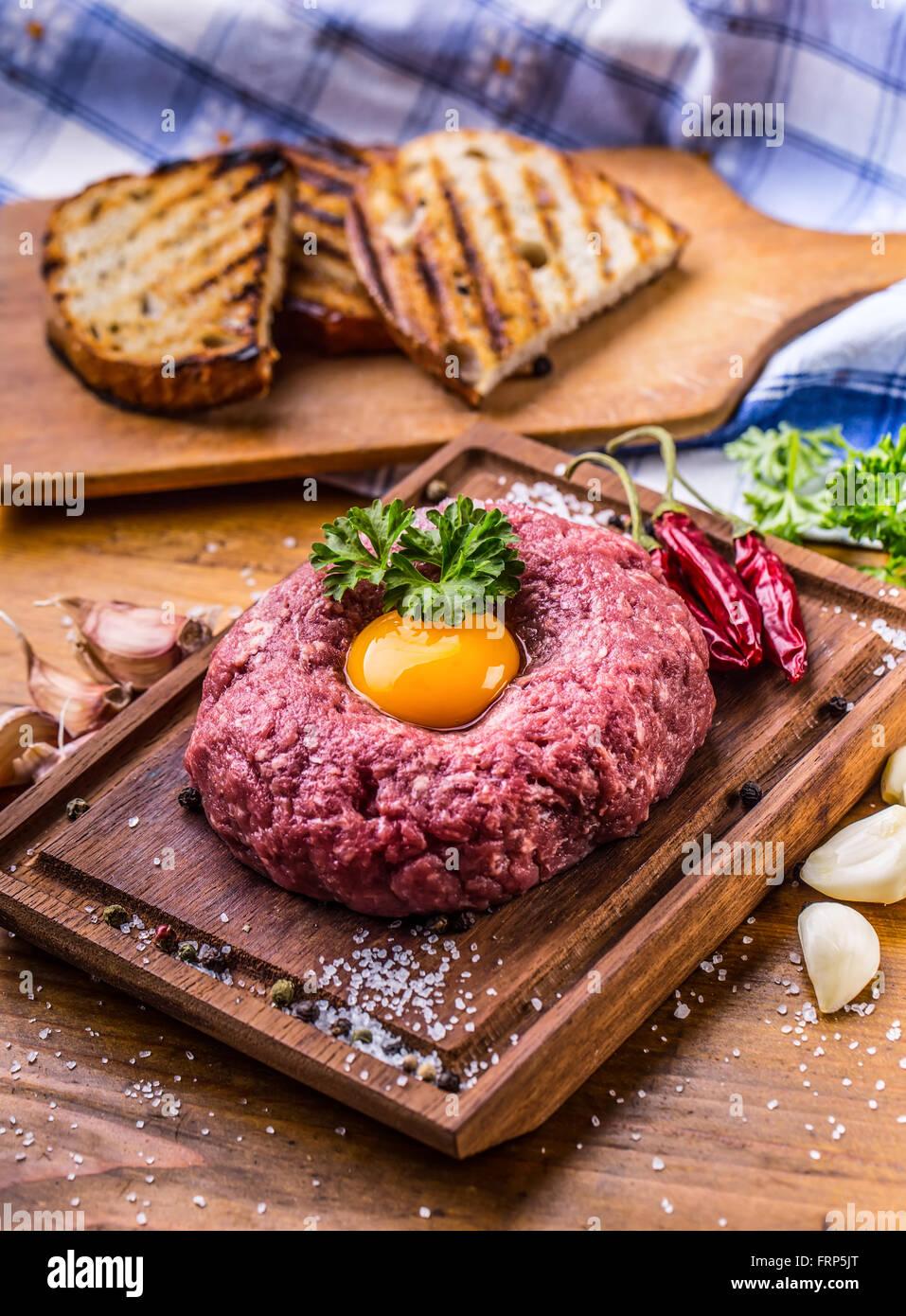 Carne di manzo crudo .gustosa tartare di manzo. Classic tartare di manzo sul tagliere in legno. Ingredienti: Materie Immagini Stock