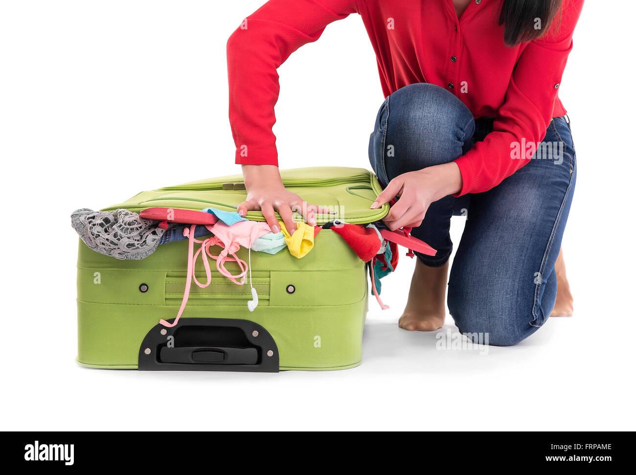 Difficile per pack traboccante valigia. Su uno sfondo bianco. Immagini Stock