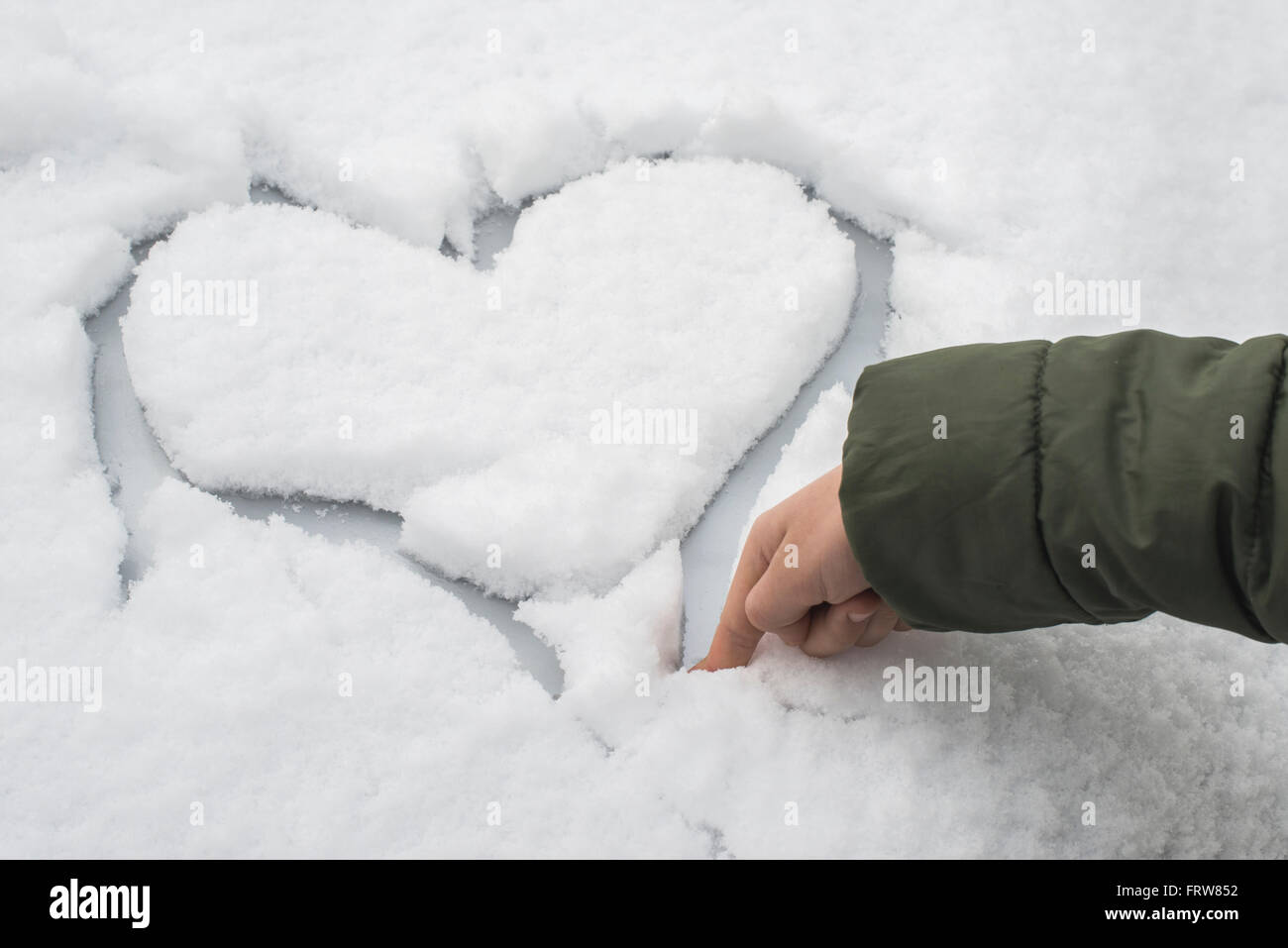Dito di Little Boy carving un cuore nella neve su una macchina Foto Stock