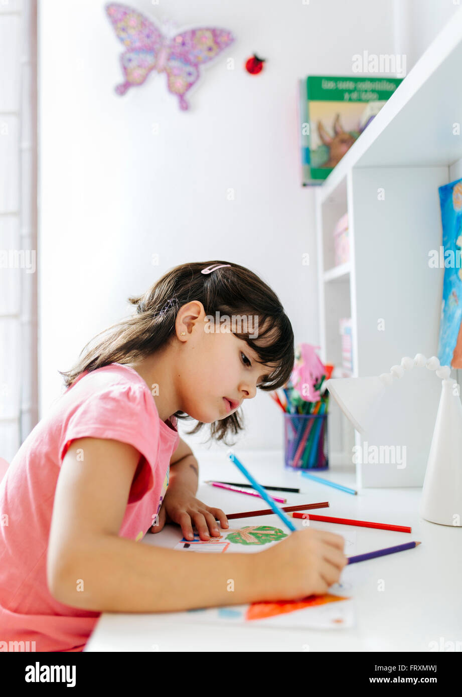 Bambina disegno sulla sua scrivania a casa Immagini Stock