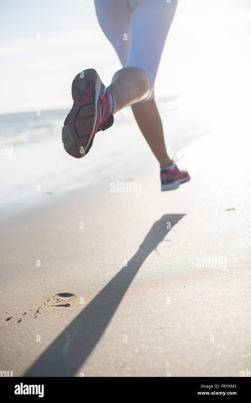 Vista posteriore di una donna dinamica in esecuzione sulla spiaggia la mattina presto lasciando tracce nella sabbia Immagini Stock
