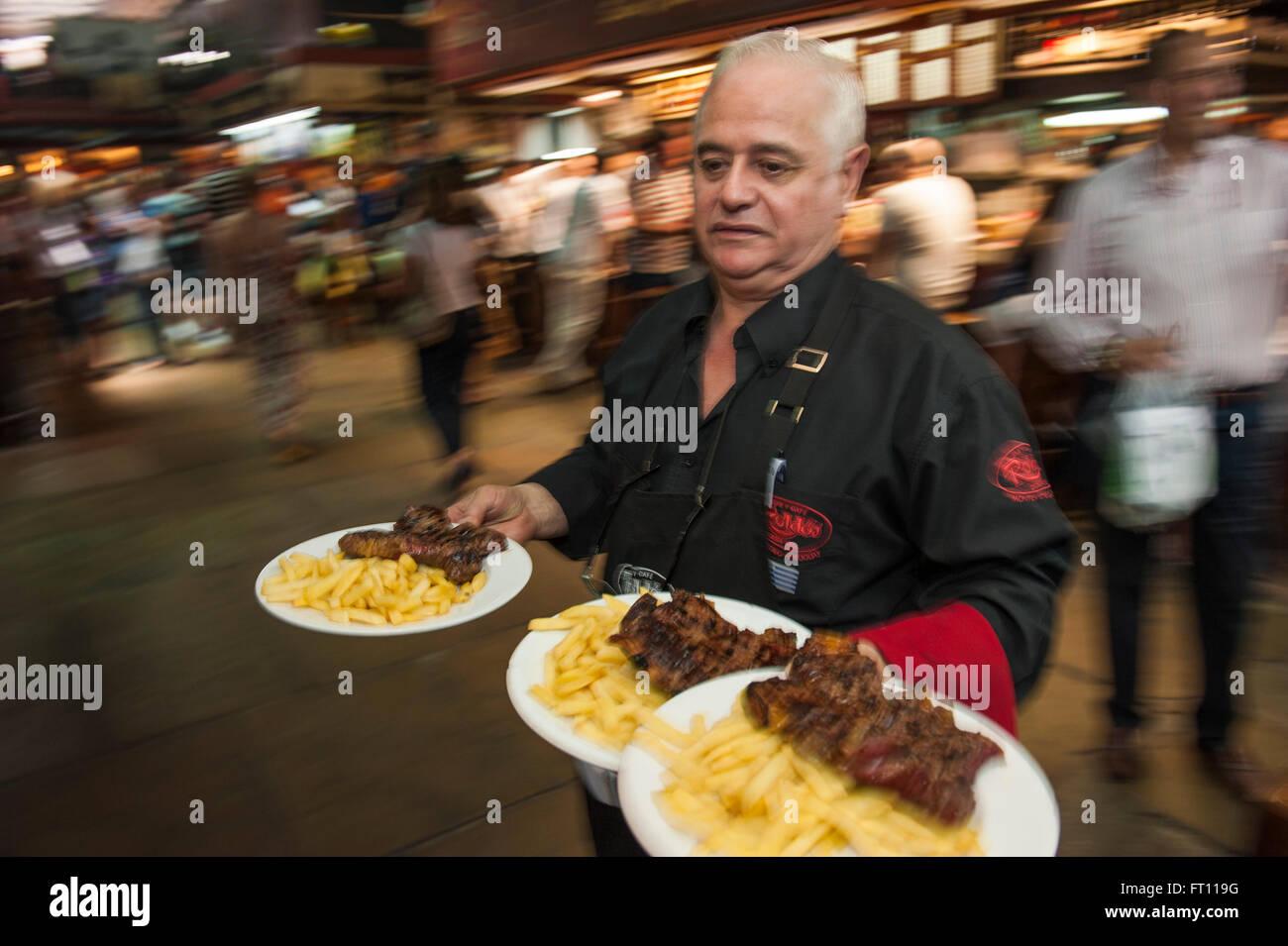 Cameriere serve bistecche e patatine fritte, Parilla tipo ristorante, Mercado del Puerto, Montevideo, Montevideo, Immagini Stock