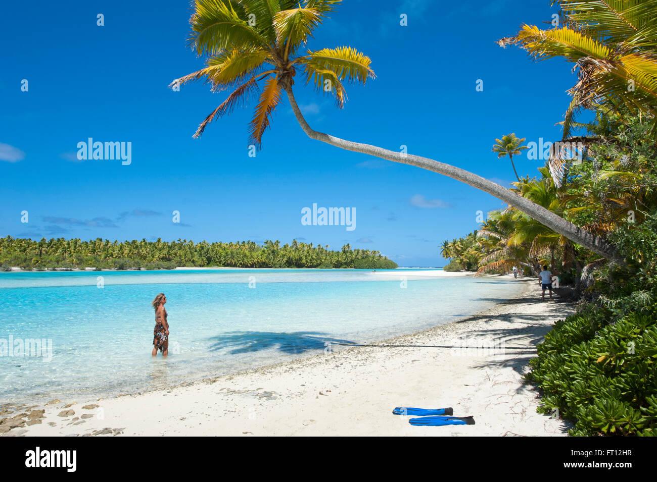 Donna passeggiando lungo la spiaggia con palme a un piede isola in Laguna Aitutaki, Aitutaki, Isole Cook, Sud Pacifico Immagini Stock