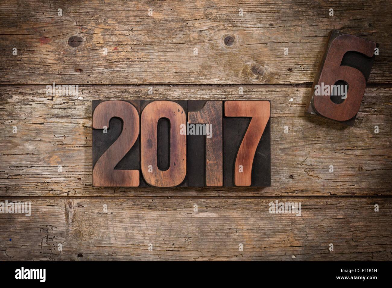 Ruotare dell'anno 2016 al 2017 raffigurata con vintage Stampa tipografica Stampa numeri di blocco sul rustico Immagini Stock
