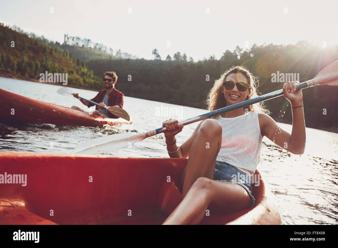 Bella giovane donna kayak in un lago con l uomo paddling in background. Coppia giovane in canoa sul giorno di estate. Immagini Stock