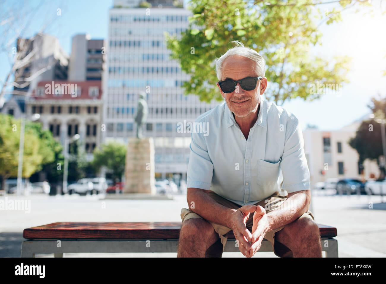 Ritratto di bello senior uomo seduto all'esterno. Maschio maturo turistico con occhiali da sole seduti fuori Immagini Stock