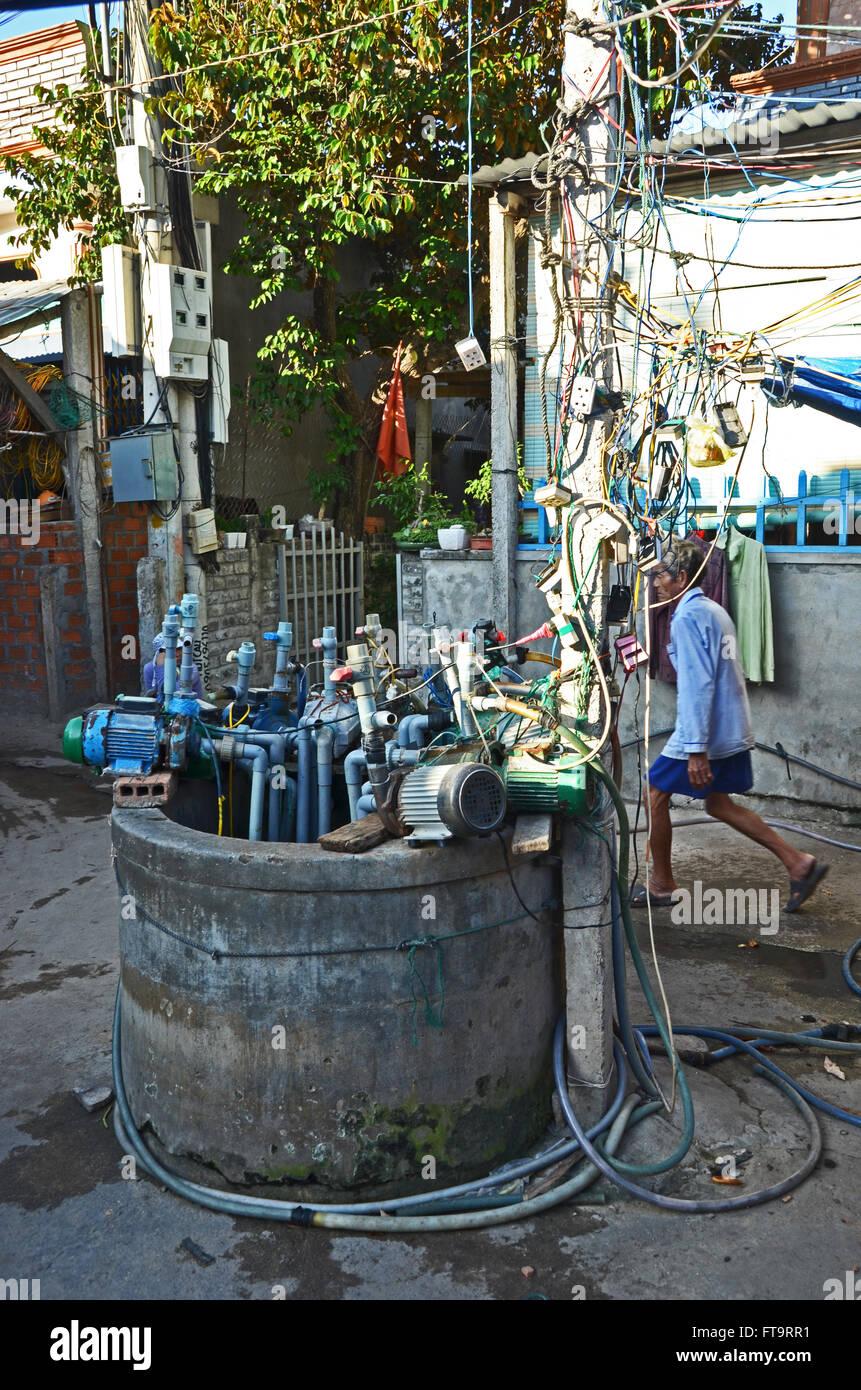Le pompe si affollano intorno alla sommità di un pozzo nel villaggio di Quy Nhon, Vietnam Immagini Stock