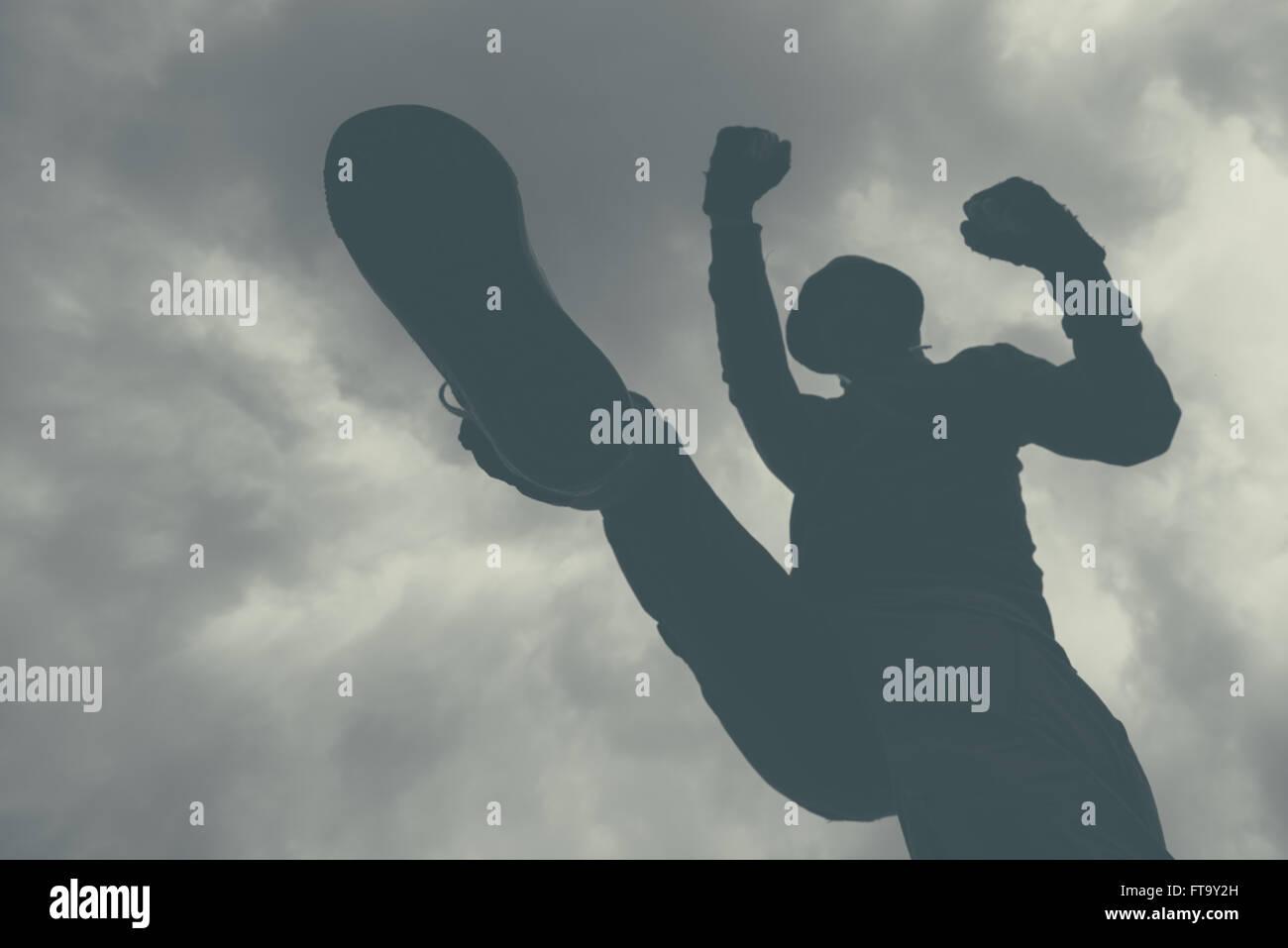 Violento attacco, irriconoscibile incappucciati criminale maschio di calci e pugni vittima sulla strada. immagine Immagini Stock
