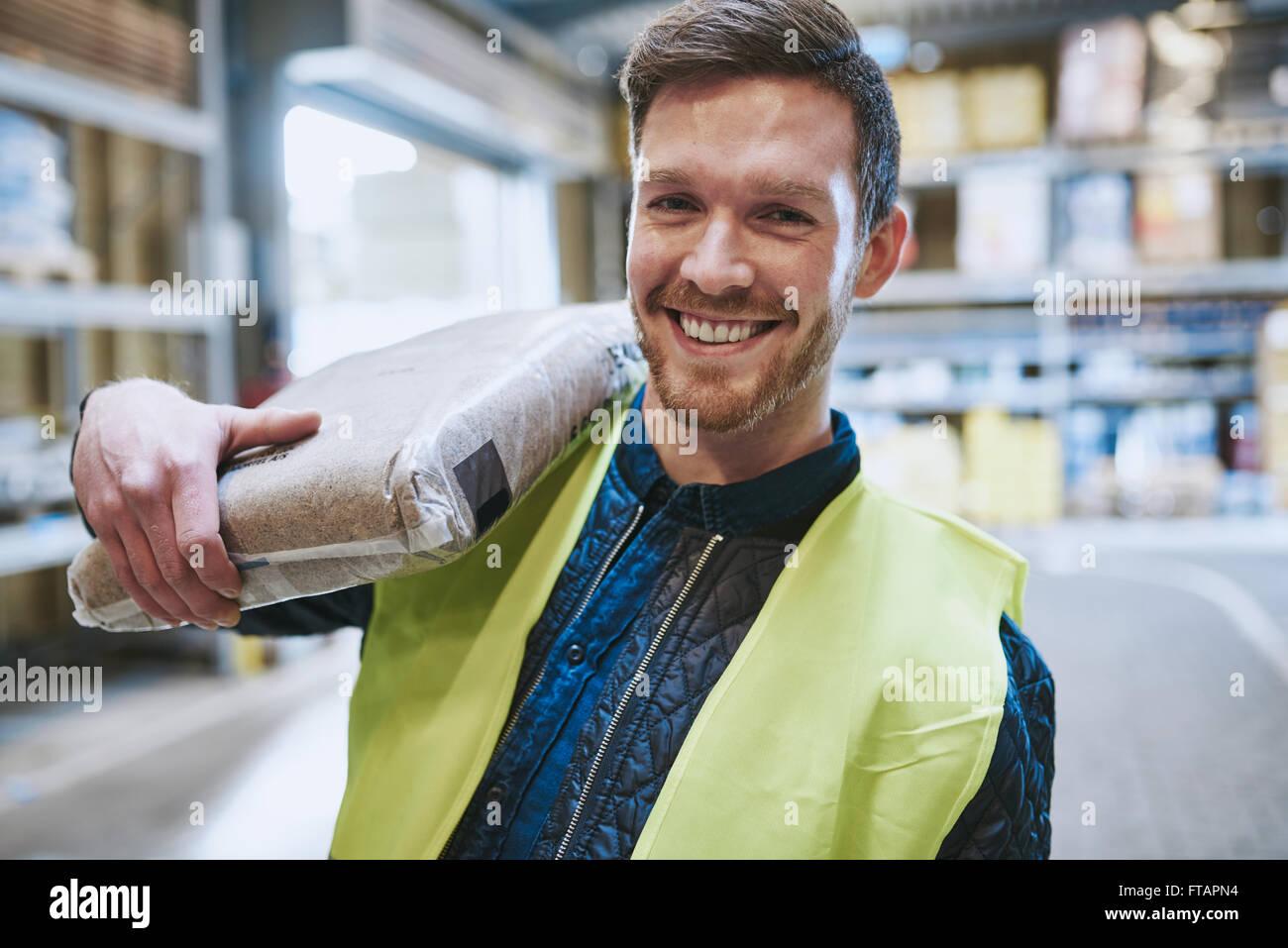 Gentile felice lavoratore del magazzino in un GIUBBETTO ALTA VISIBILITA in piedi nel magazzino con una sacca di Immagini Stock