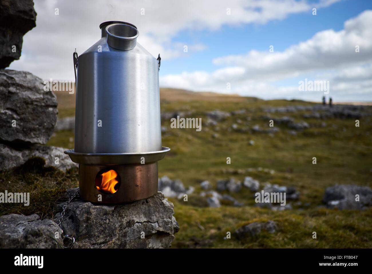 Un bollitore stufa burning mostra fiamme nella scatola di fuoco seduto su una roccia con rock e di erba in background. Immagini Stock