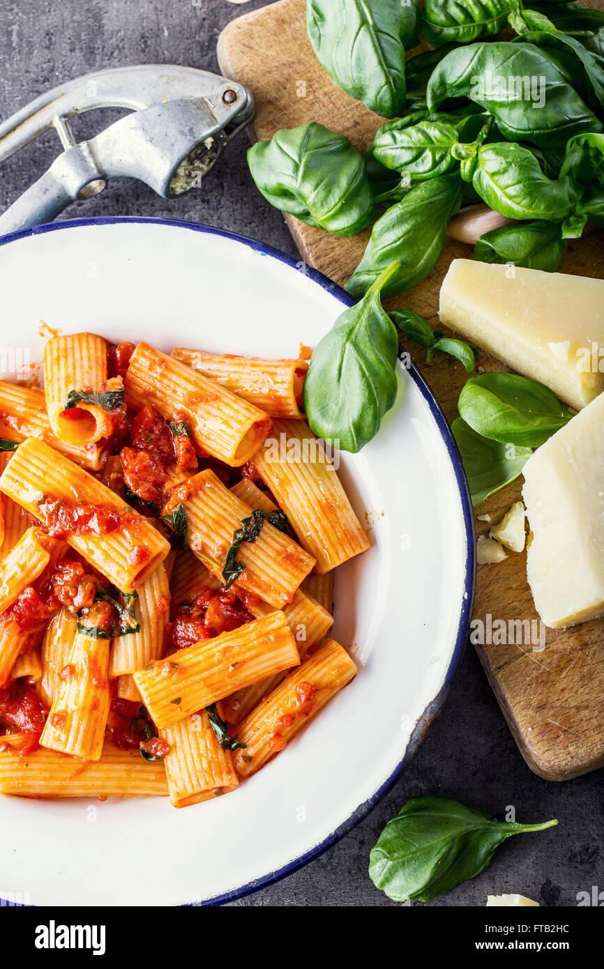 La pasta. Cucina italiana e mediterranea. Pasta Rigatoni con salsa di pomodoro foglie di basilico e aglio formaggio Immagini Stock