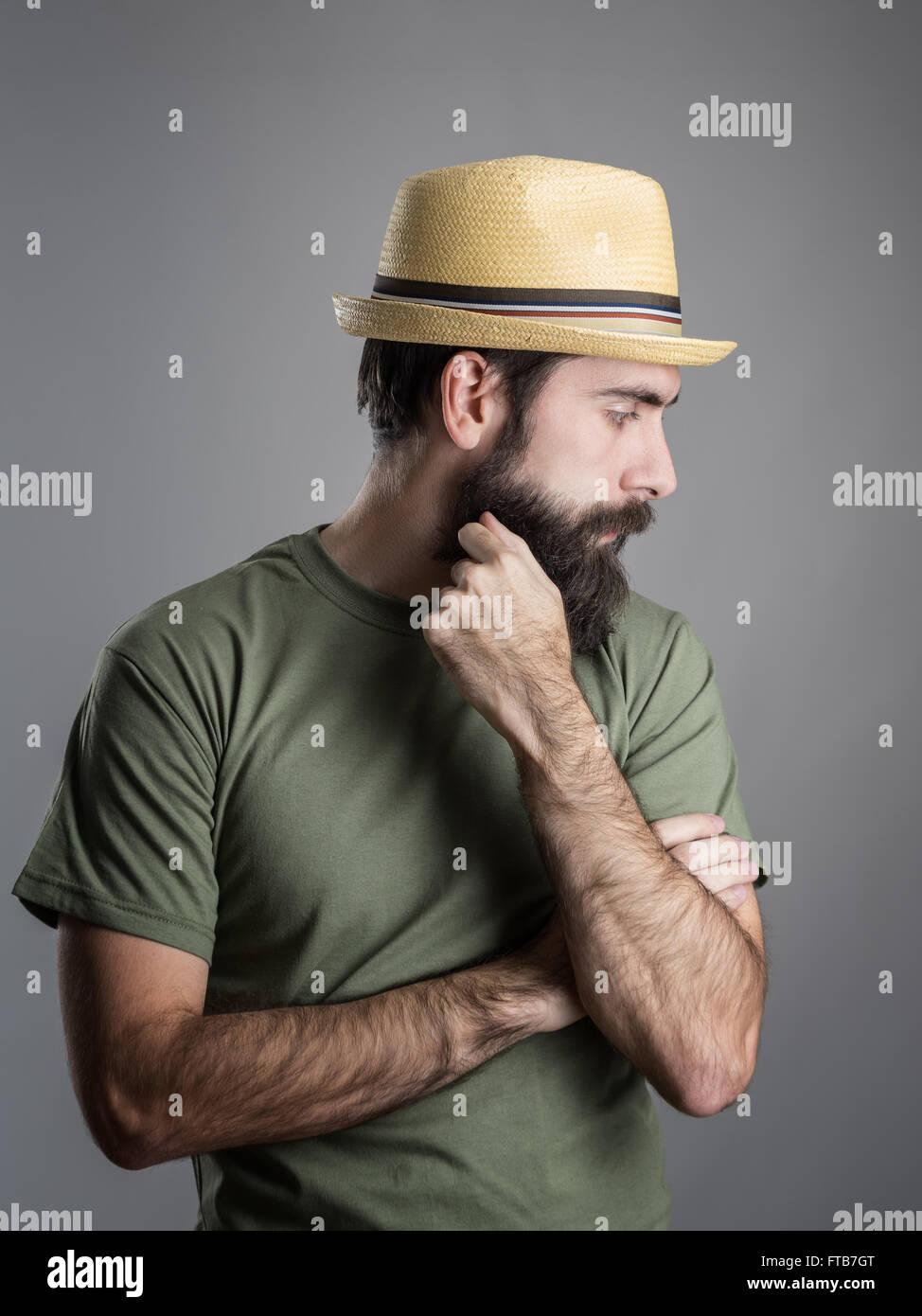 Vista di profilo di triste uomo barbuto che indossa cappello di paglia che  guarda lontano. Headshot ritratto su studio grigio Sfondo con vignette. 466793941fc9