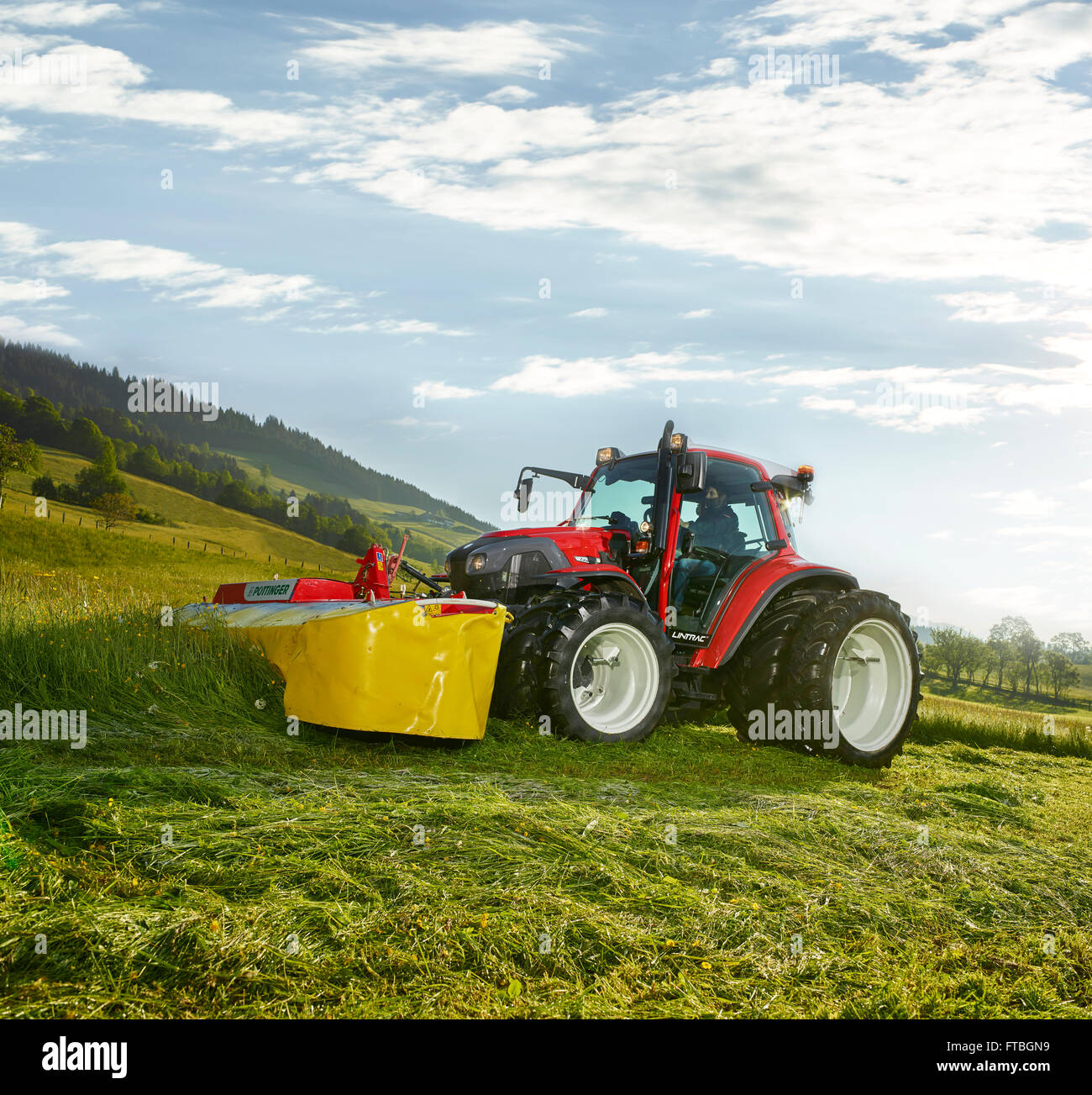 Trattore con ruote gemellate la falciatura di un campo, Hopfgarten, Brixental Tirolo, Austria Immagini Stock