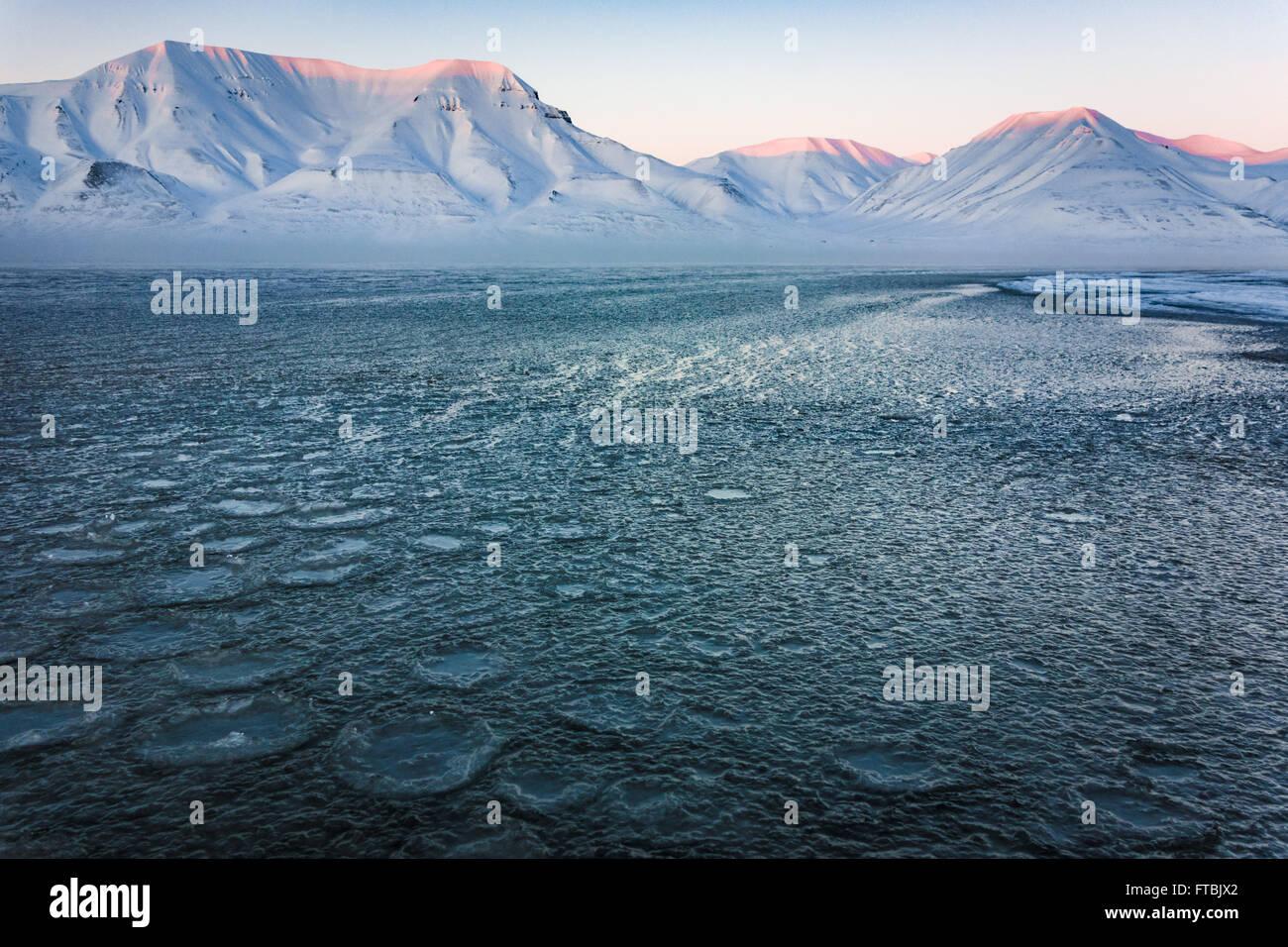 Tramonto litorale congelati a Sjøskrenten spiaggia con vedute Hiorthfjellet, Longyearbyen, Spitsbergen, Svalbard. Immagini Stock