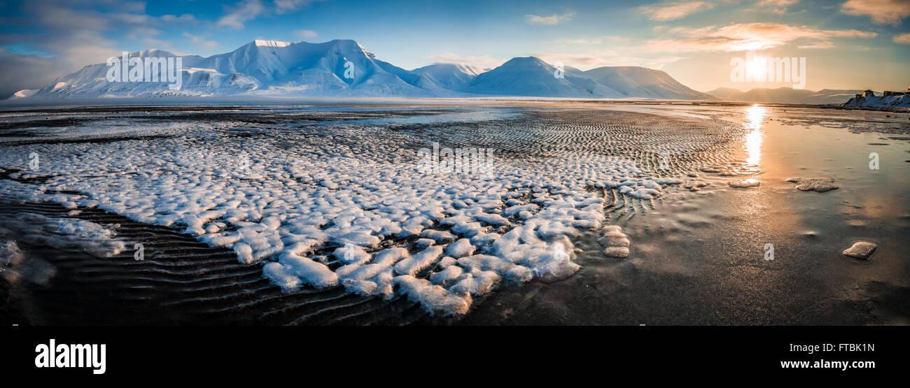 Sunrise formazioni di ghiaccio sulla spiaggia Sjøskrenten con vedute Hiorthfjellet, Longyearbyen, Spitsbergen, Svalbard. Foto Stock