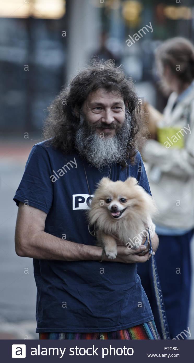 Un dai lunghi capelli uomo barbuto che indossa una maglietta blu, detiene un marrone chiaro, crema di Pomerania Immagini Stock