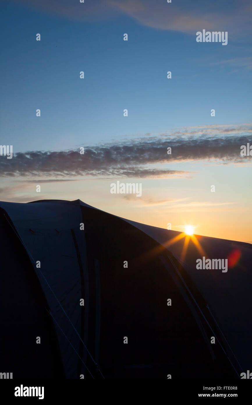 Il sole sorge o imposta su una tenda piantato in un campo, spesso usato per le vacanze o per vacanze nonché Immagini Stock