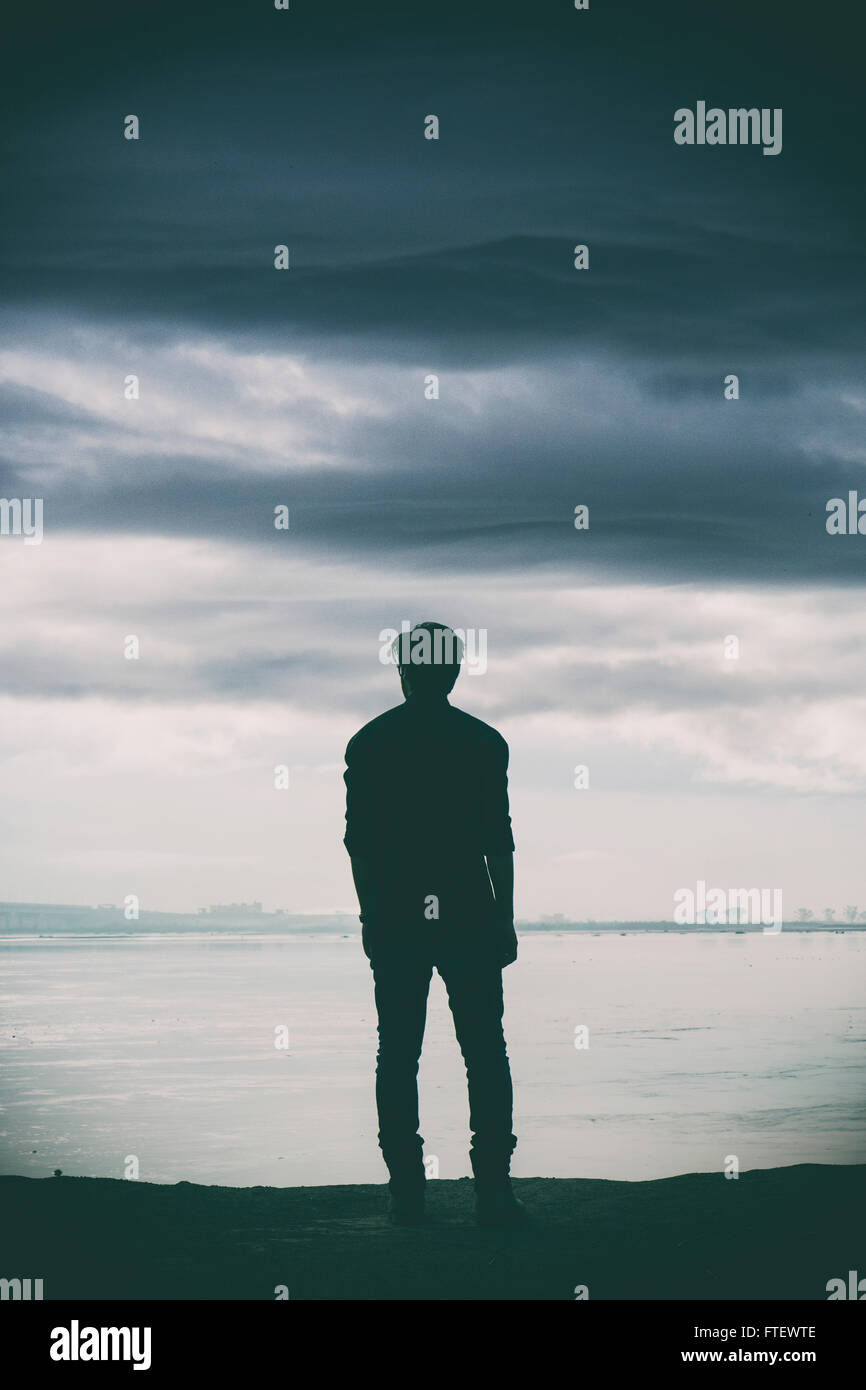 Uomo in piedi dal fiume Immagini Stock