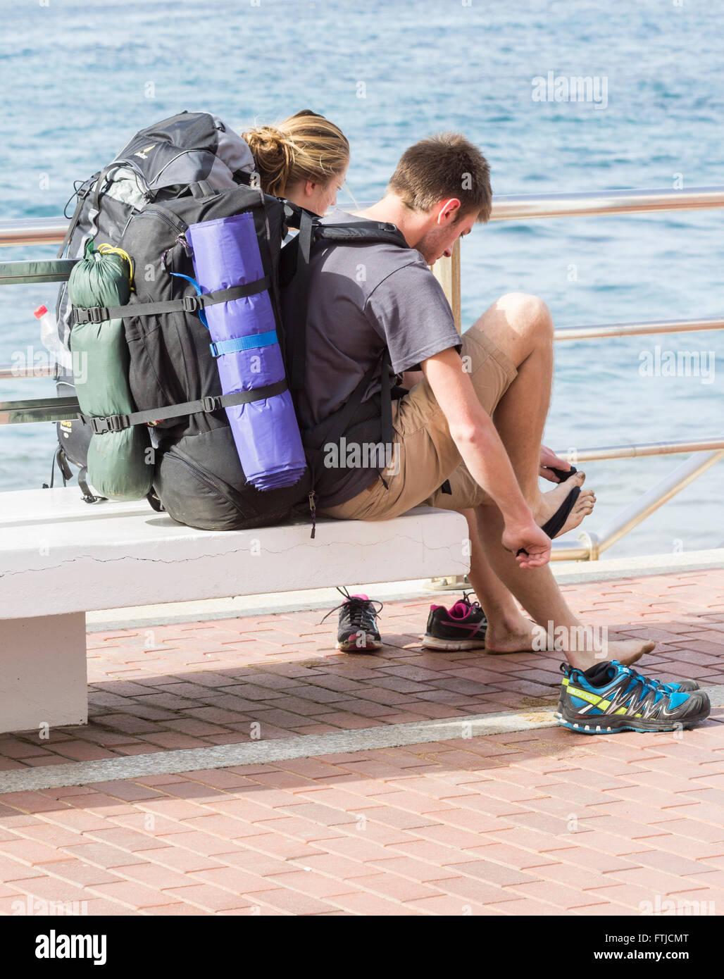Maschio e femmina backpackers affacciato sulla spiaggia. Immagini Stock