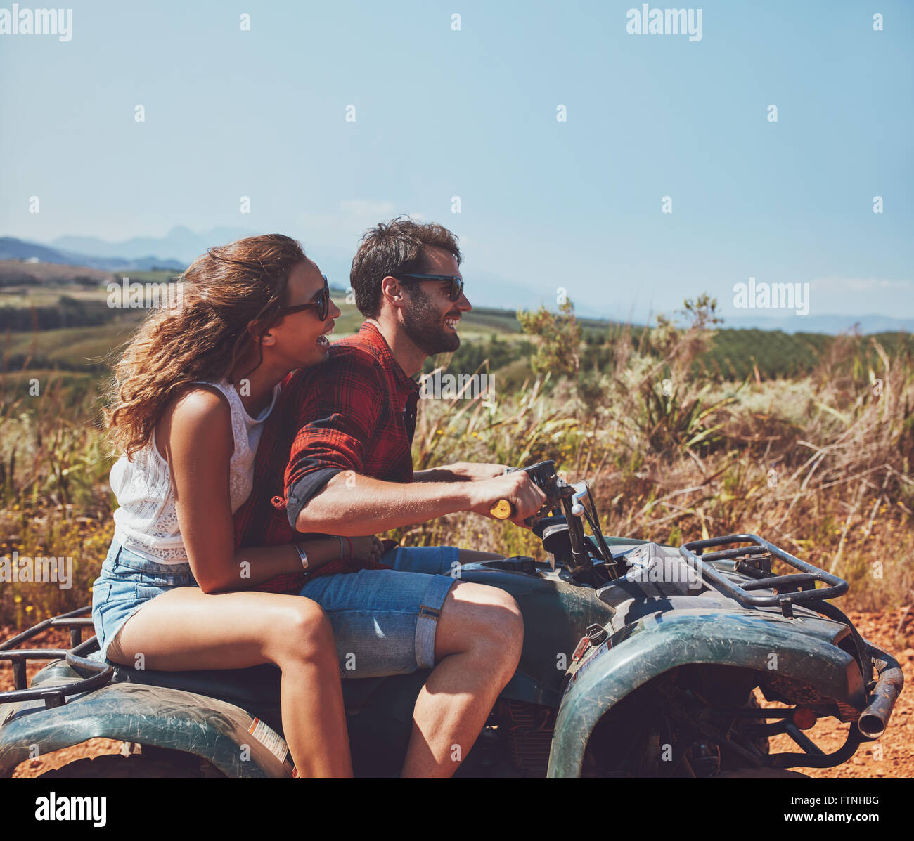 Vista laterale del giovane uomo e donna in sella a una moto quad su una vacanza estiva. Giovane godendo le vacanze Immagini Stock