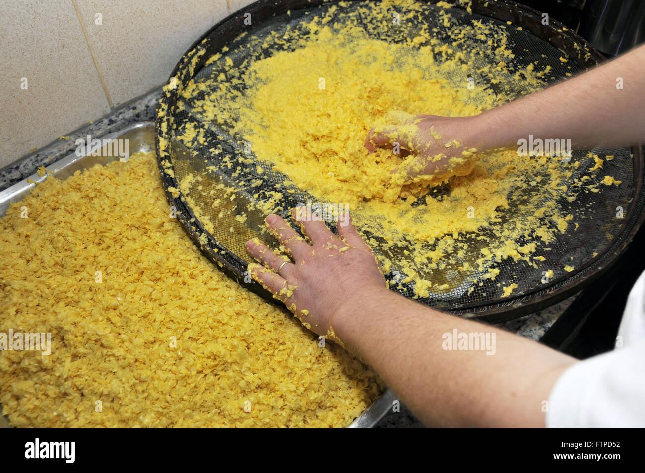 Donna di vagliatura per produzione di polenta di mais - cittadina rurale di São João Batista Gloria Immagini Stock