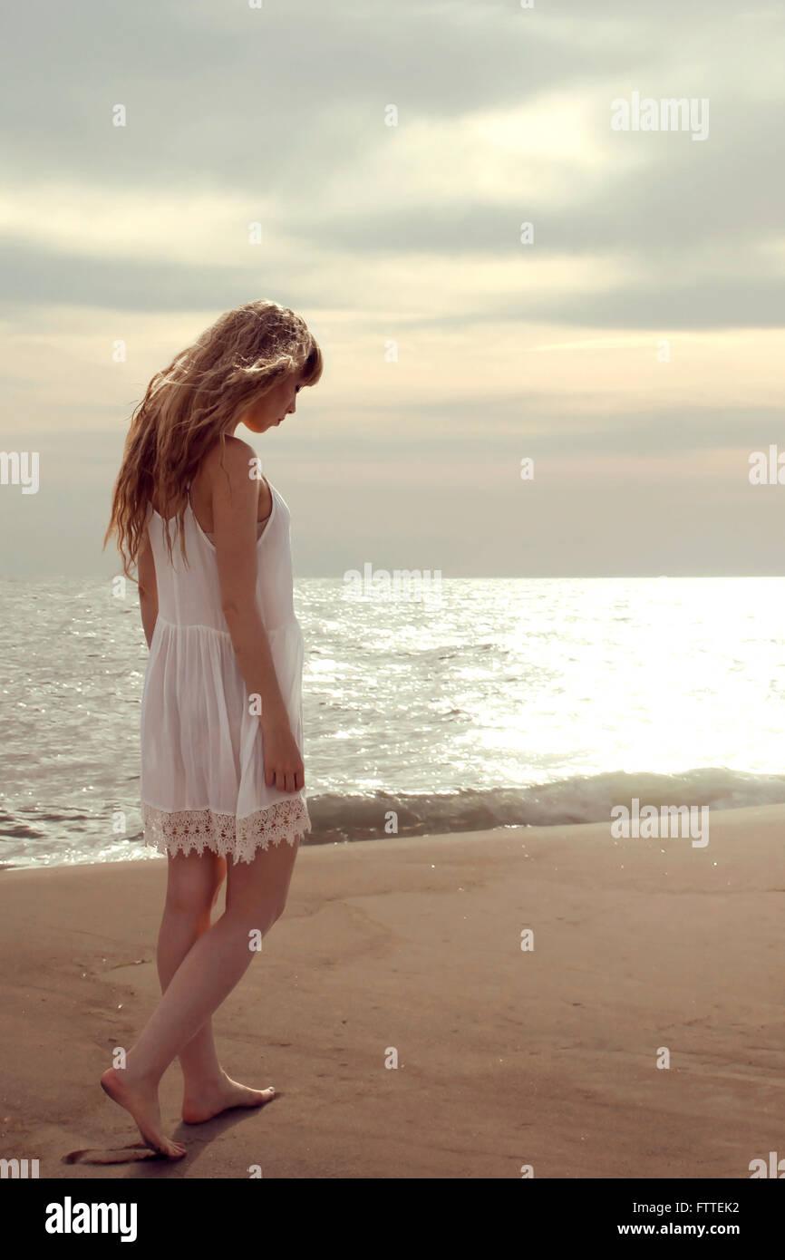 Donna bionda camminando sulla spiaggia guardando verso il basso Immagini Stock
