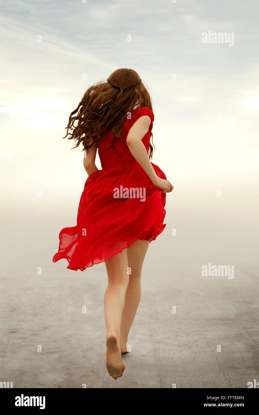 Donna in abito rosso acceso lontano Foto Stock