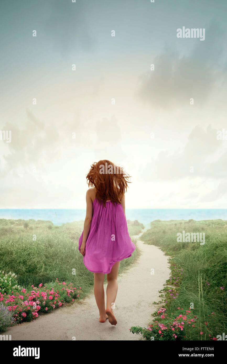 Donna che cammina sulla spiaggia fiorita Foto Stock