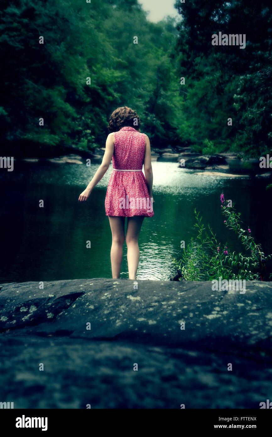 Donna in abito corto al lago Foto Stock