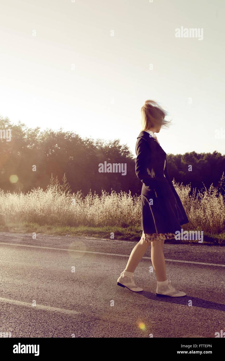 Anni Cinquanta giovane donna camminando sulla strada Immagini Stock