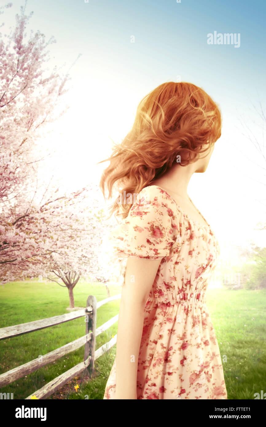 Donna su un ventoso giorno di primavera, guardando lontano Foto Stock