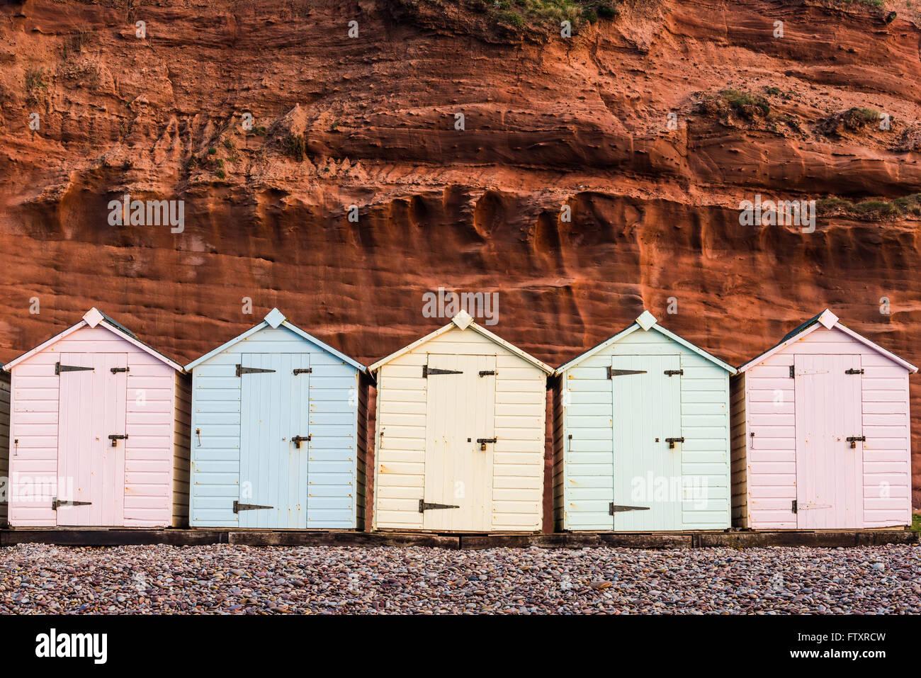 Beach Hut fila in colori pastello, roccia rossa sfondo, South Devon, Regno Unito Immagini Stock