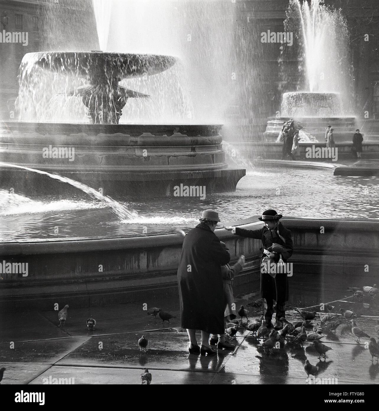 Anni Cinquanta storiche, nonna con grand bambini alimentando i piccioni da fontane a Trafalgar Square a Londra. Immagini Stock