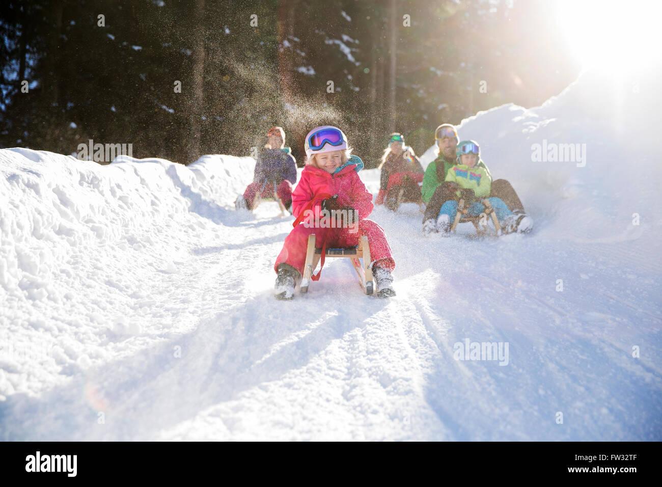 Le bambine e i bambini a cavallo delle slitte con la loro famiglia, Muttereralm Innsbruck in Tirolo, Austria Immagini Stock