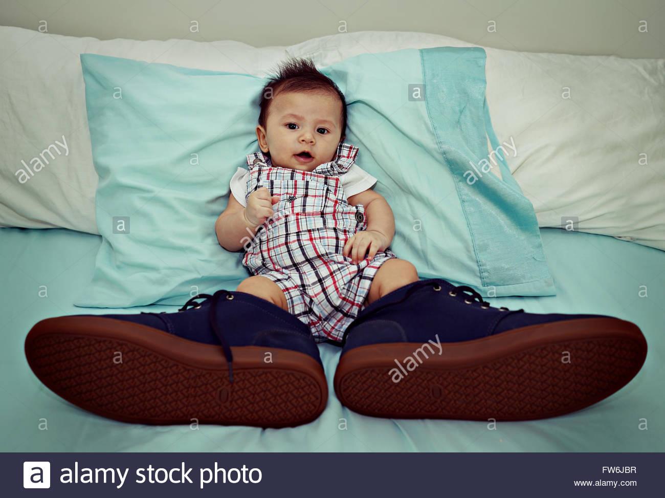 Bambino asiatico indossando scarpe di grandi dimensioni sul letto Immagini Stock