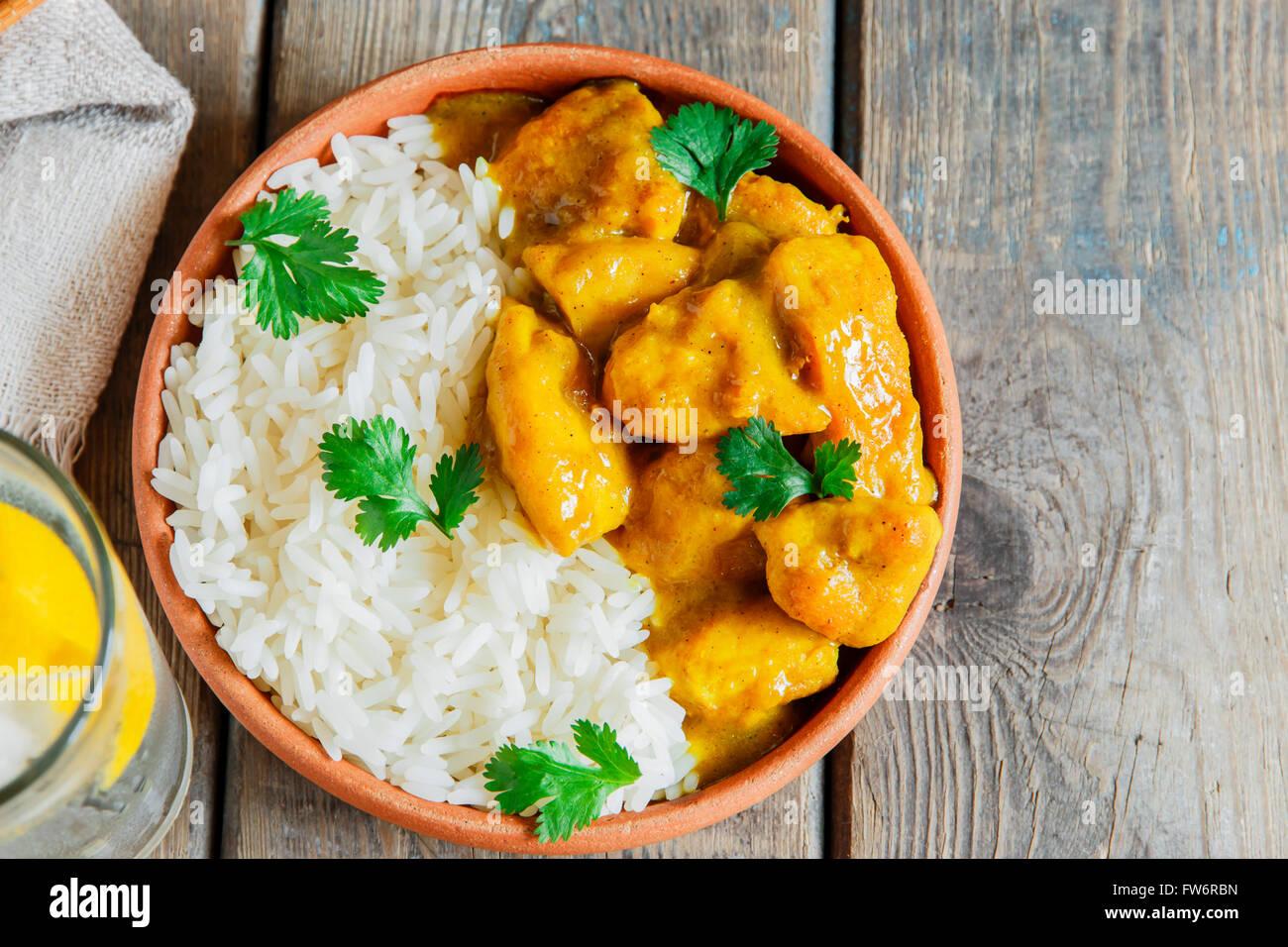 Pollo al curry con riso su una superficie in legno Immagini Stock