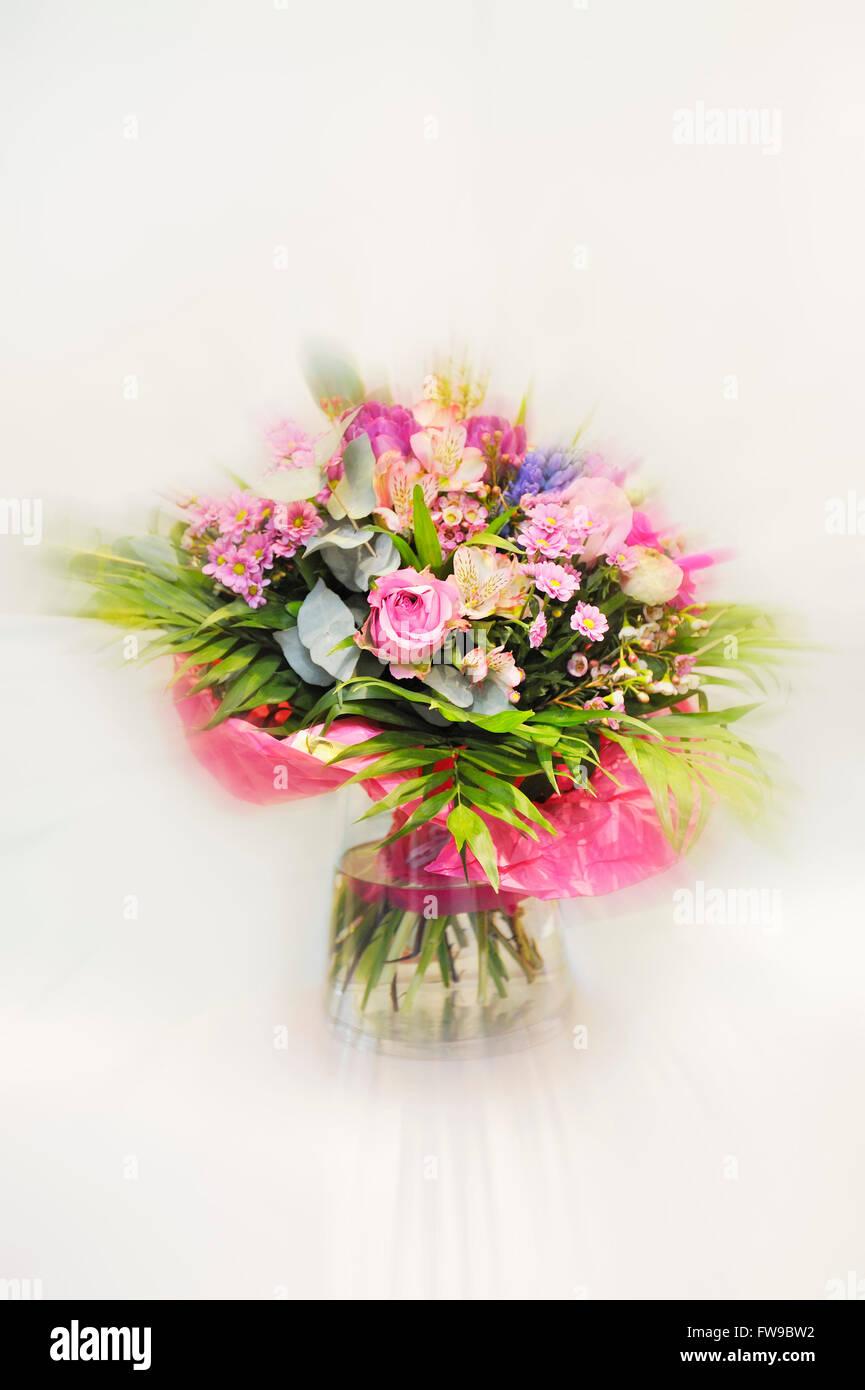 Mazzo di fiori in un vaso di vetro contro uno sfondo bianco Immagini Stock