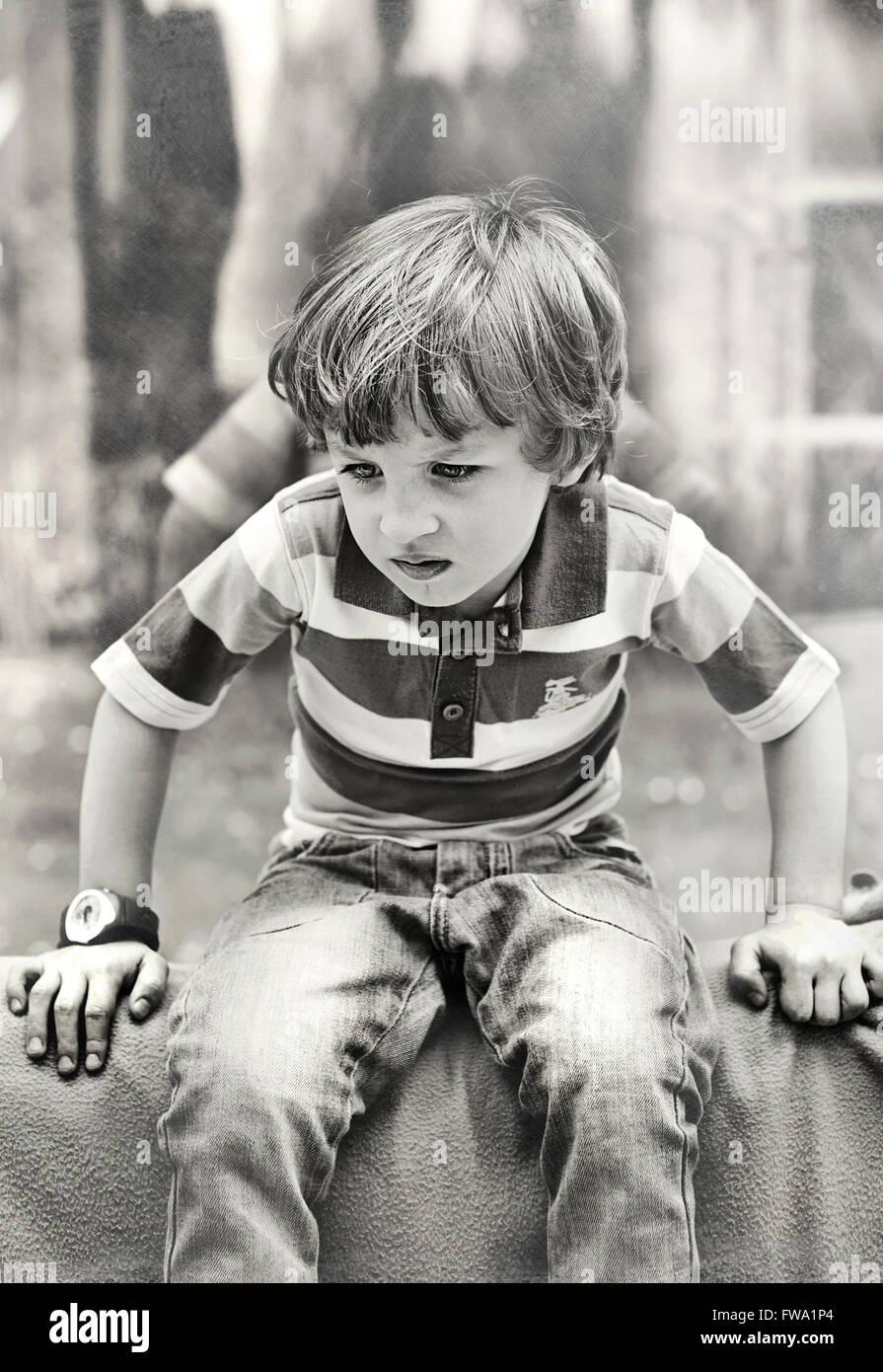 Arrabbiato piccolo ragazzo giocando Foto Stock