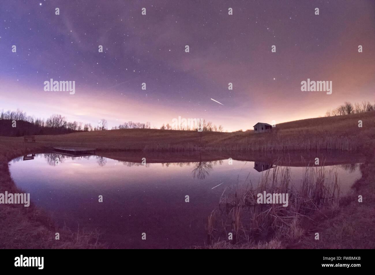 La stazione spaziale internazionale striature nel cielo notturno appena dopo il crepuscolo riflessa da un laghetto. Immagini Stock
