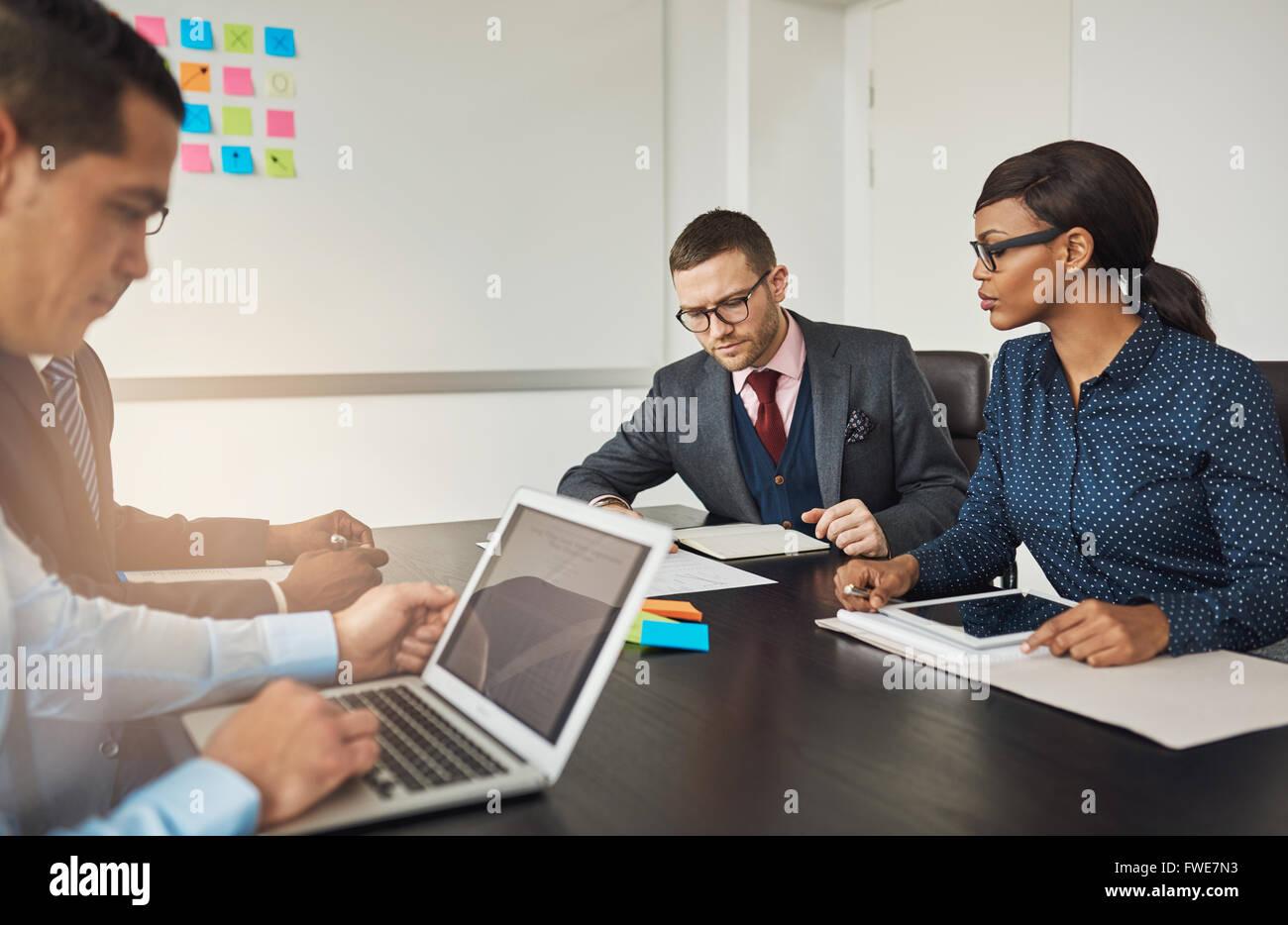 Gruppo di multirazziale colleghi di lavoro in occasione di un incontro seduti attorno ad un tavolo nel lavoro di Foto Stock