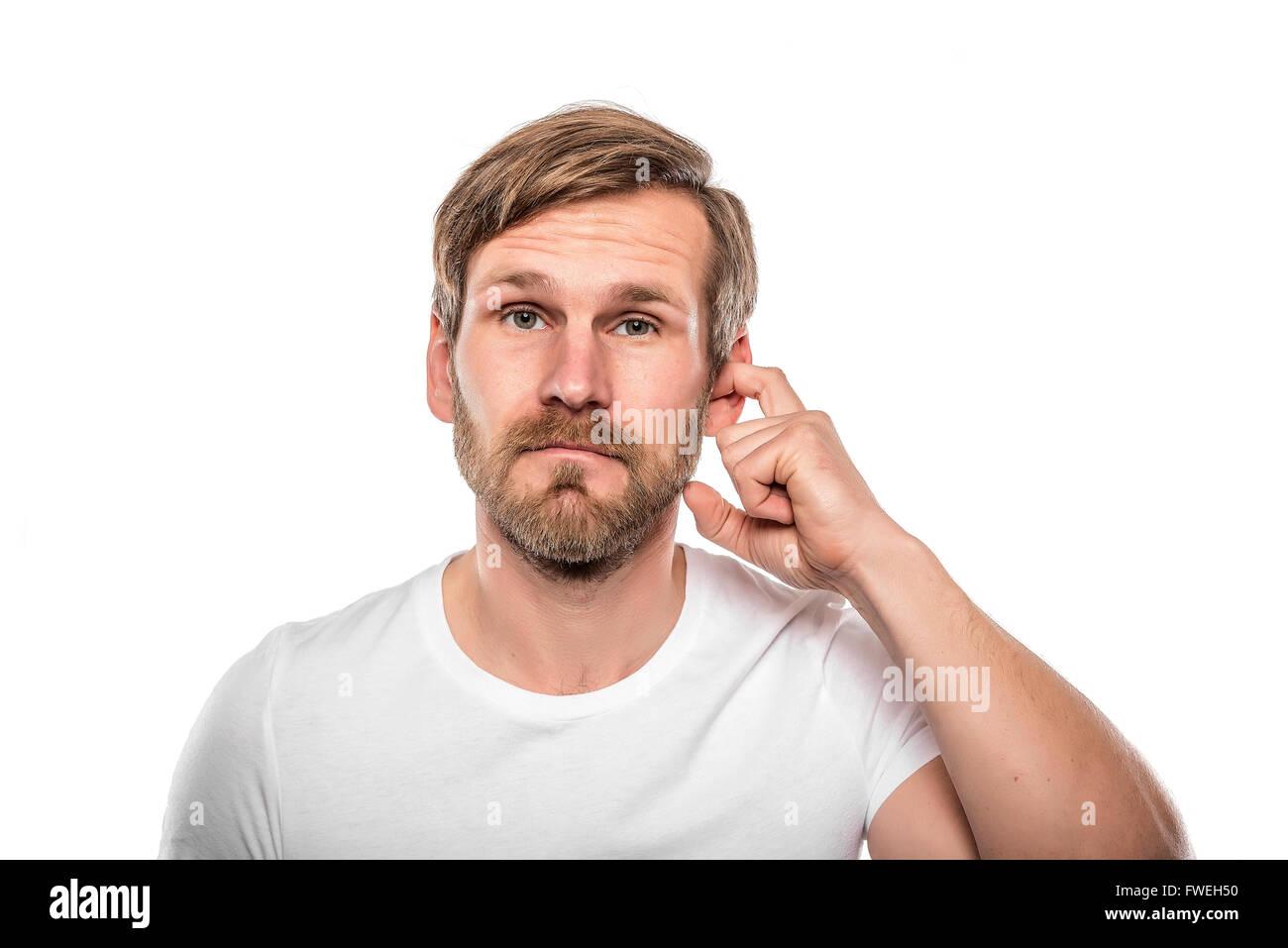 Uomo di graffiare nel suo orecchio. Isolato su bianco. Immagini Stock