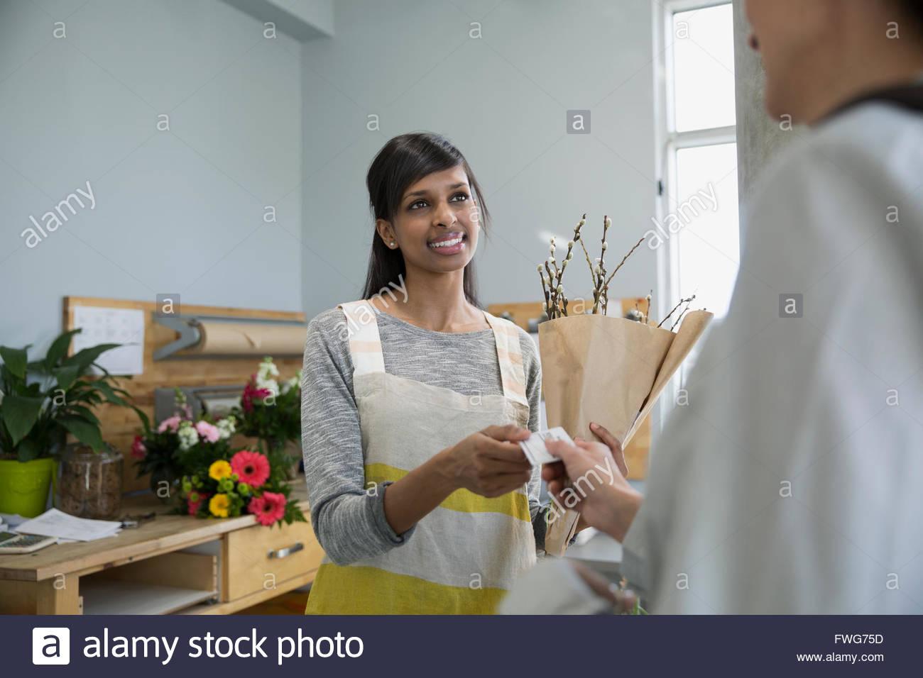 Donna fiorista pagando con carta di credito negozio di fiori Immagini Stock