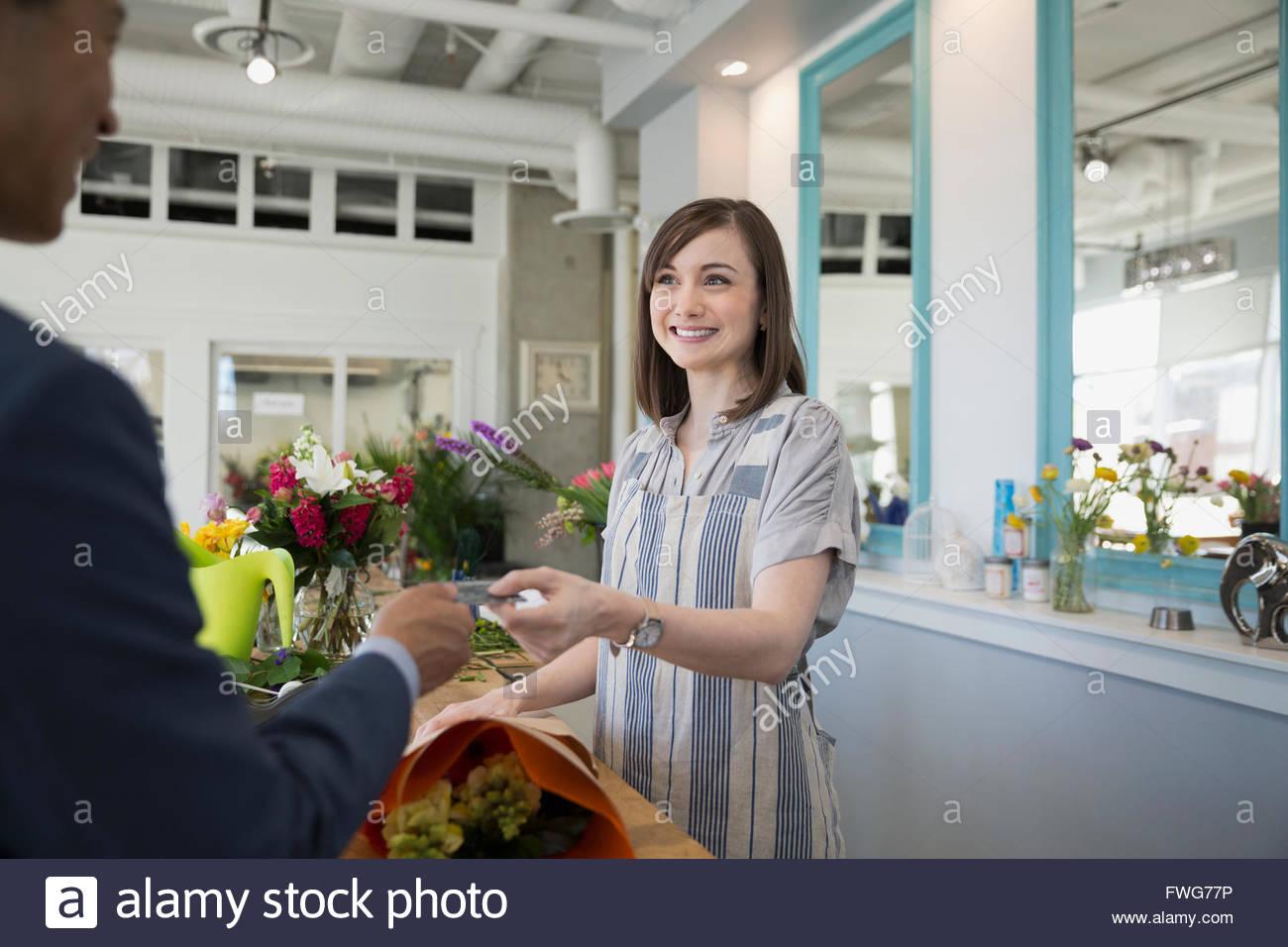 Uomo fioraio di pagamento con carta di credito negozio di fiori Immagini Stock