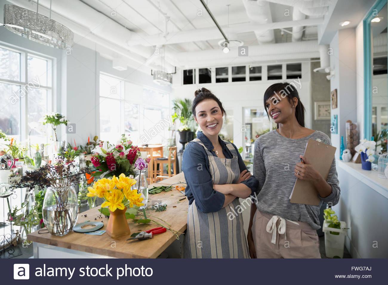 Fioristi sorridente nel negozio di fiori Immagini Stock